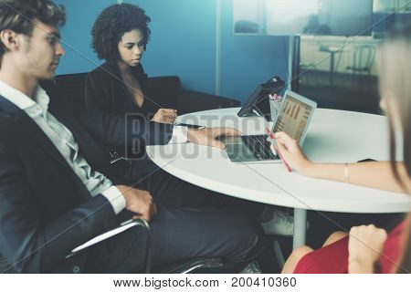 View of meeting room in office settings with group of people having work meeting: caucasian handsome man employer brazilian young woman probationer and caucasian female co-worker laptop on the table