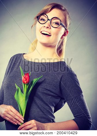 Happiness and satisfaction with life. Blonde woman wearing eyeglasses with single red green tulip. Happy joy girl feeling spring time holding beautiful flower.