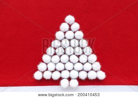 White Christmas tree out of glittery snowballs arranged on red felt as Christmas background.