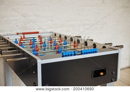 Detailed close up picture of foosball table with metall rods with red and blue foos men players figures in empty room with white blank copyspace wall for your advertisement or promotional content