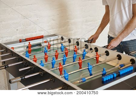 People leisure entertainment fun and tabletop games concept. Unrecognizable male kicker enjoying foosball match moving foosball rods with blue men figures back and forth. Selective focus poster