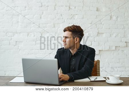 Picture of handsome stylish young Caucasian CEO with bristle wearing formal suit working on generic laptop pc at his modern workplace looking sideways with thoughtful expression on his face