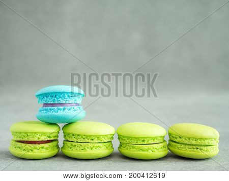 Blue color macaroon stand over assortment of green macaroon with copy space on bare cement or concrete wall background