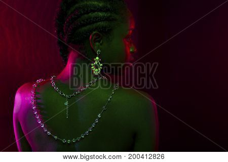 Colorful and creative portrait of an beautiful african womans bare back with necklace and jewelry. Dark skin and braided hair on red lit background.