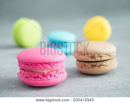 Closeup stack of colorful macaroons on glass with copy space on bare cement or concrete wall background