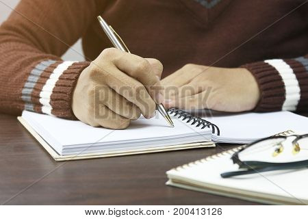 hand of people student writing and note on notebook on wood table with copy space in library concept as education attempt and make effort to win intend to improve knowledge for future life
