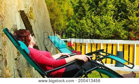 Woman relaxing on sunbed or deck chair in her garden during sunny weather.