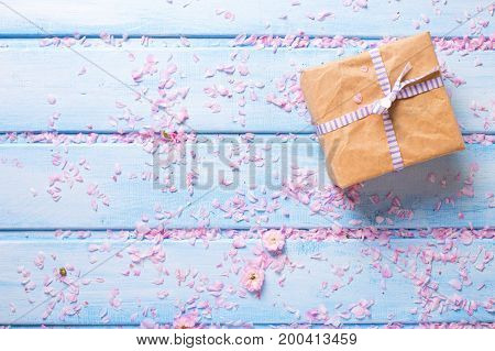 Wrapped box with present and sakura pink flowers on blue wooden planks. Selective focus. Place for text. Top view.