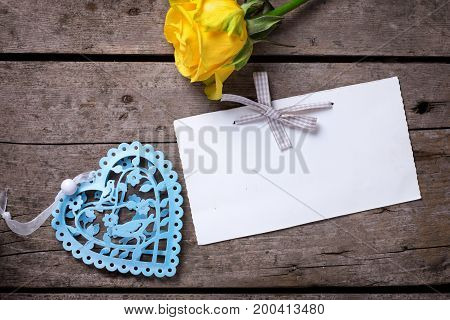 Beautiful yellow rose decorative heart and tag on vintage wooden background. Selective focus. Place for text. Top view.