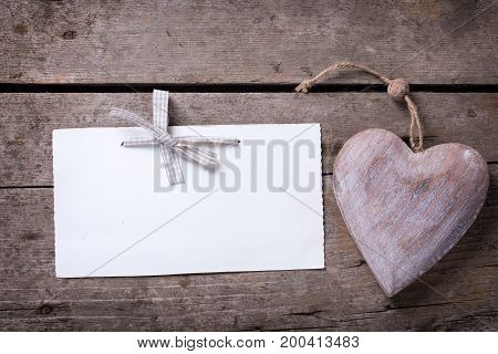 Empty tag with bow and decorative heart on rustic wooden background. Top view. Place for text. Selective focus.