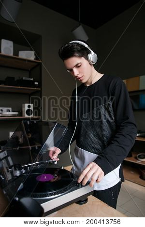 Music shop. Vinyl records buying. Young male listening to audio in headphones, modern turntable