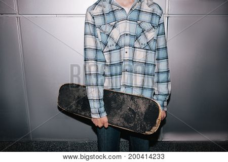 Skateboarder with skateboard. Street style. Modern youth closeup, subculture for young people, unrecognizable male