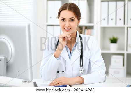 Latin american doctor woman standing with arms crossed and smiling at hospital. Physician ready to examine patient.  Health care, insurance and help concept. Physician ready to examine patient