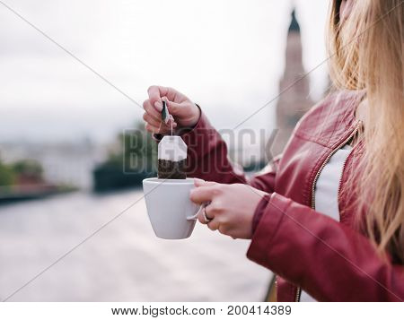 Tea party in fresh air. Rest at nature, cup and tea bag, unrecognizable woman