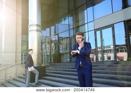 Businessman waiting for his colleague outside looking at the watch