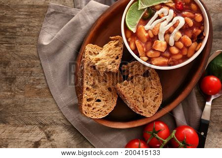 Composition with delicious turkey chili in bowl on wooden table