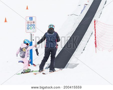 Sochi - March 28 2017: A woman and a child in skiing go to the ski travolator to climb to the top of the mountain March 28 2017 Sochi Russia