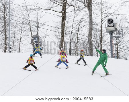 Sochi - March 28 2017: Children in mountain skiing learn to ski with a coach in green uniforms in the mountains March 28 2017 Sochi Russia