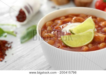 Bowl with delicious turkey chili on wooden table, closeup