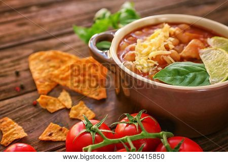Delicious turkey chili in casserole on wooden table