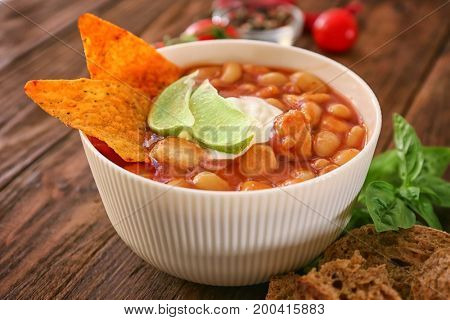 Bowl with delicious turkey chili on wooden table