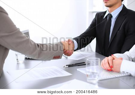Business people shaking hands, finishing up a meeting. Copy space at the left corner.