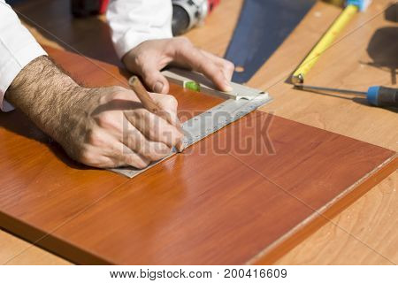 Carpenter's hands indicate the dimension on the board with a pencil and an angle.