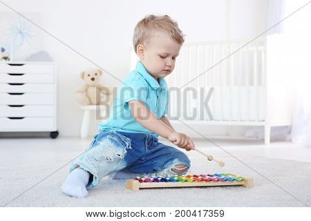 Cute little boy with xylophone at home