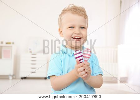 Cute little boy with pair of maracas at home