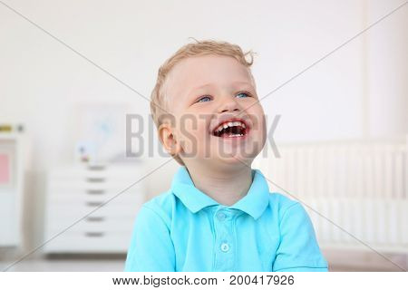 Cute little boy laughing at home
