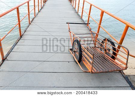Orange handcart parked on pier walkway with iron railings Handcart used for carriage of goods to ship.