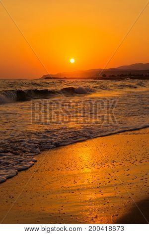 View on a deserted Beach in the colorful Light of a beautiful Sunrise. Close-up of long Beach at Sunrise. Beach Background.