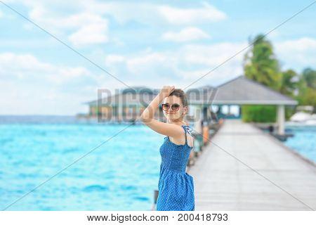 Beautiful young woman on pontoon at sea resort