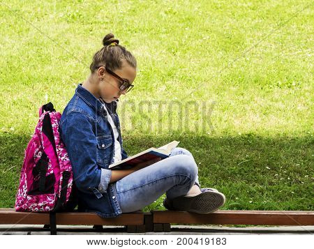 Beautiful blonde schoolgirl girl in jeans shirt reading a book on grass with a backpack in the park on a sunny summer day Education. School. College.
