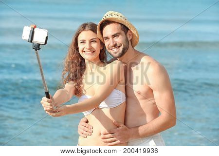Beautiful young couple taking selfie at sea resort