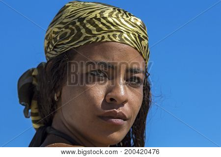 Portrait of Young Arab Woman. A headshot of a young woman wearing silk scarf and looking at camera against blue sky.