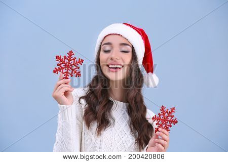Pretty lady in Christmas hat holding red snowflakes on color background