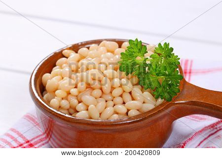 saucepan of canned white beans on checkered dishtowel - close up