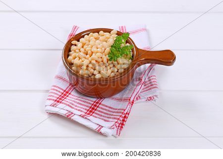 saucepan of canned white beans on checkered dishtowel