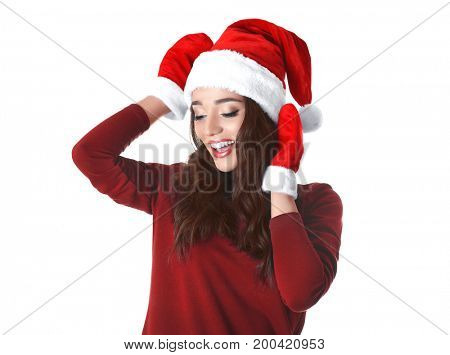Beautiful emotional woman in Christmas hat and red winter gloves on white background