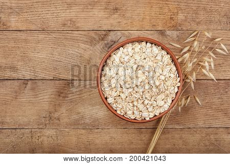 oat flakes in bowl and oat ear on wooden table top view. Uncooked oatmeal
