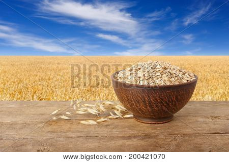 uncooked oatmeal in bowl and ears of oats on wooden table with field on the background. Ripe field, blue sky with beautiful clouds