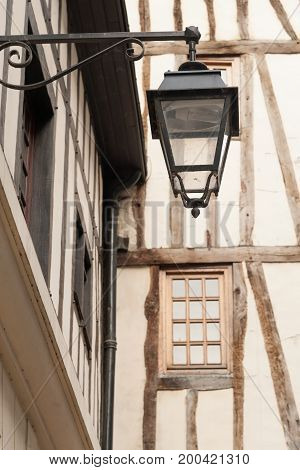 Street lamp on old timberframe house in Rouen, France