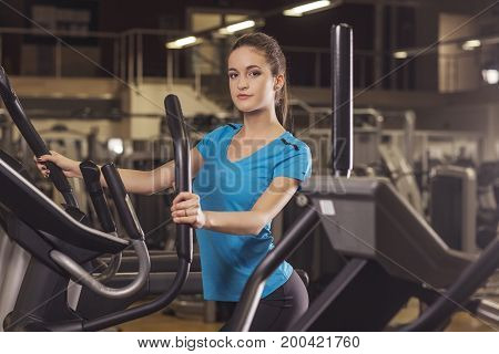 Young Fit Woman Using An Elliptic Trainer In A Fitness Center, Back Shot. Portrait Of Fitness Girl I