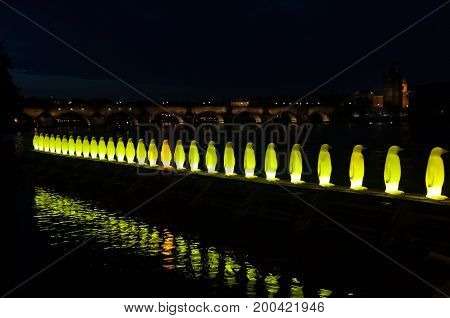 PRAGUE, CZECH REPUBLIC - July 16, 2017: Giant Chair Sculpture and Penguins Sculpture at night on the Bank of River Vltava at Kampa Museum in Prague.