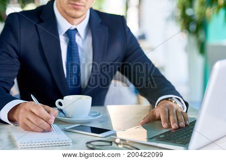 Closeup portrait of unrecognizable successful businessman working at desk making notes while planning startup project