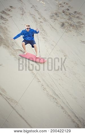 Thrill-seeking mid adult male riding a board down a sand dune hill having fun playing outdoors while on vacation. Living life to its fullest