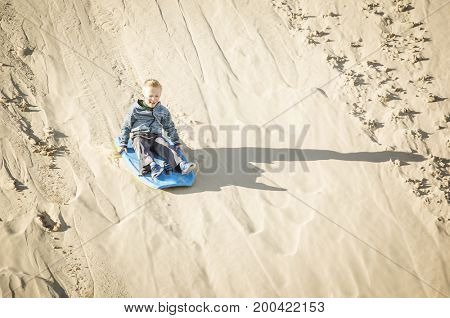 thrill-seeking young child riding a board down a sand dune hill having fun playing outdoors while on vacation. Cute boy Living life to its fullest
