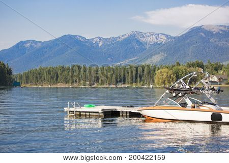 Beautiful summer scene of a motor boat parked at a boat dock on a beautiful, scenic mountain lake. Blue skies, blue mountains, blue water