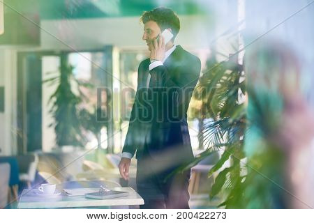Side view portrait of young startup entrepreneur speaking by phone and smiling  standing behind glass wall in cafe
